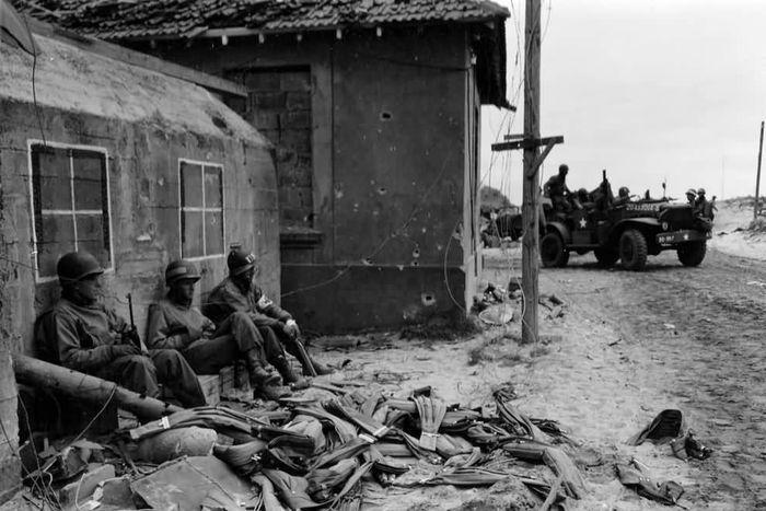 Американские солдаты отдыхают у немецкого бункера, замаскированного под дом