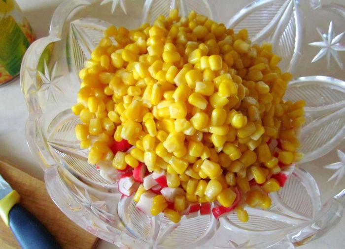 Высыпаем в салатницу измельченные крабовые палочки и консервированную кукурузу