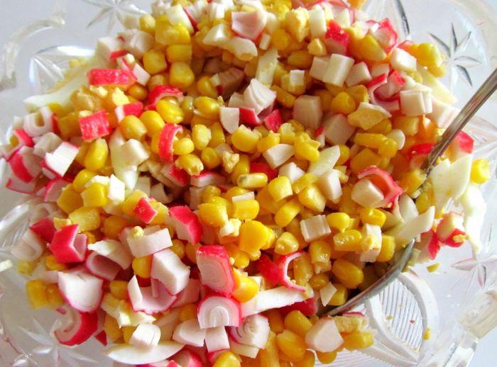 Высыпаем измельченные яйца в салатницу и перемешиваем с кукурузой и крабовыми палочками