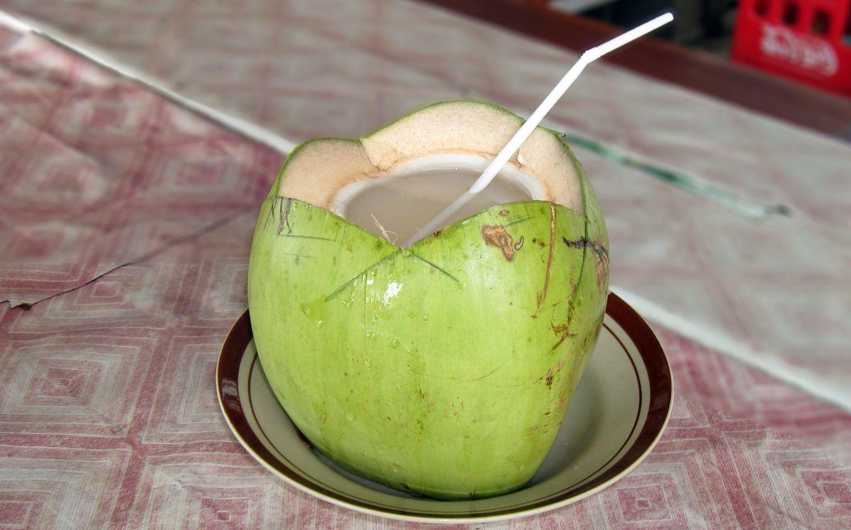 Открытый свежий кокос в котором видна прозрачная кокосовая вода