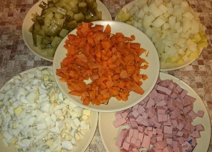 Нарезаем мелко вареную картошку, вареные яйца, соленые огурцы и колбасу