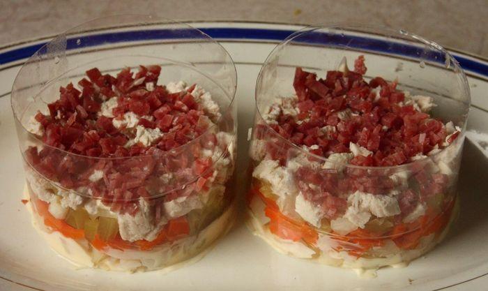 Добавляем в салат слой мелко порезанной копченой колбасы