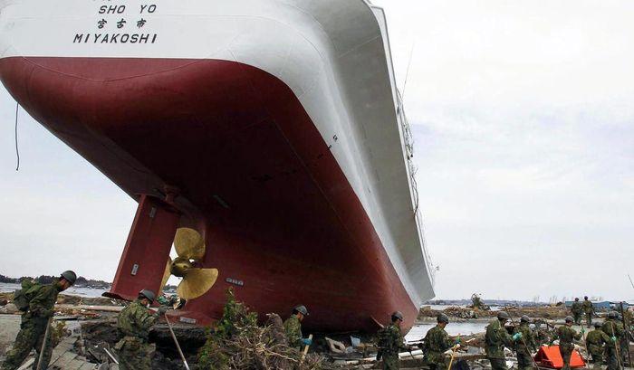 Японские спасатели на фоне выброшенного на сушу корабля в префектура Мияги