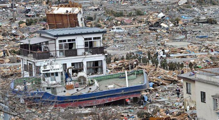 Японские спасатели проходят около выброшенного на сушу судна в городе Офунато